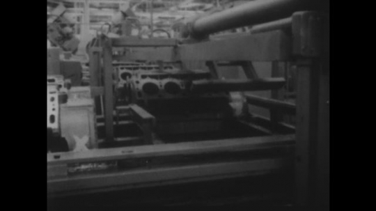 UNITED STATES 1950s: Machine parts moving in factory / Engine block in machine / Machine assembles engine / Machine assembles engine /  Engine block in machine / Close up of engine block.