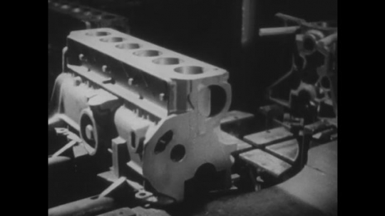 UNITED STATES 1950s: Engine block rotating in machine / Machine parts moving / Machine parts moving / Man operates machines in factory.