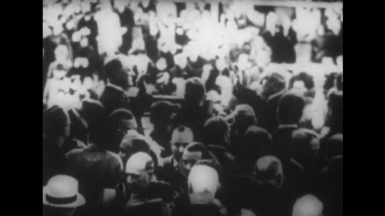 United States: 1930s:Men in crowd. Election crowd. Roosevelt speaks to crowd. Flag in street. Man escorts lady down the stairs. Man kidnaps lady. Man in crowd.