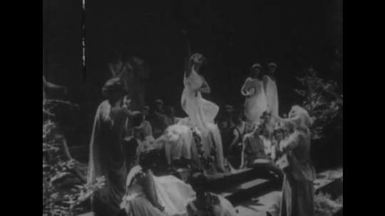 United States: 1930s: 1920's theatrical performance. Ladies dance on stage. Lady in large hat. Ruth St Denis contemporary dances outdoors. Russian composer arrives in America and smiles at camera.