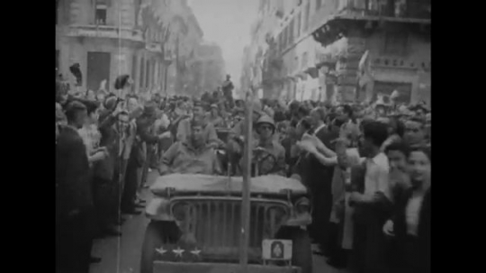 ITALY: 1940s: crowd in street wave flags at military vehicle. People cheer and celebrate in city. Lady kisses soldier