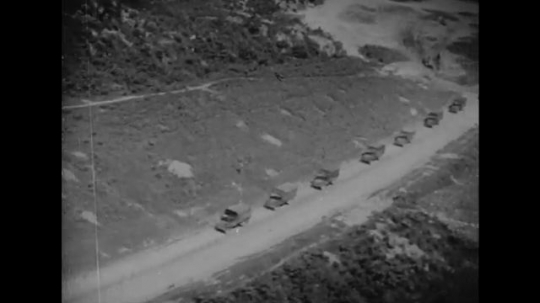 ITALY: 1940s: view of military vehicles from above. Soldiers take cover. Soldiers fire weapons