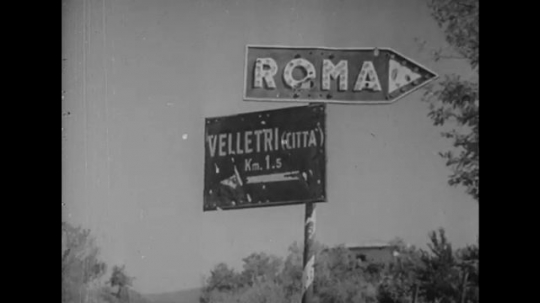 ITALY: 1940s: street sign for Rome. Tanks and vehicles in street. Soldiers march on track. Close up of soldier