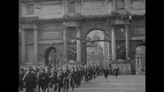 ITALY: 1940s: soldiers march through city. People carry flags. Unrest in streets. Man in uniform.