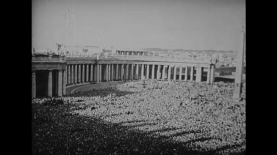 ITALY: 1940s: crowds gather in city square. Bell rings on building. View of Rome from above.