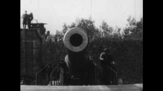 United States: 1940s: View down barrel of canon gun. Men marching in band. Men on horseback. Vehicles outside home. Soldiers lined up outside house. Firemen with hose. Man in uniform. Sailor with gun.