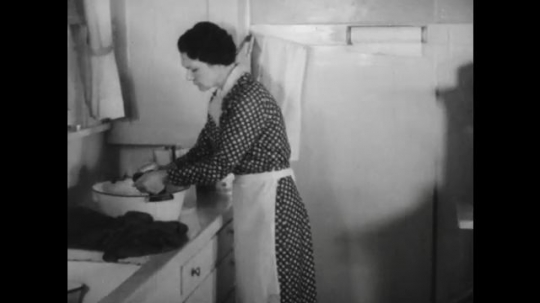 United States: 1940s: Lady washes at kitchen sink. Kettle on stove. Stove catches fire. Lady pours chemicals in washing.