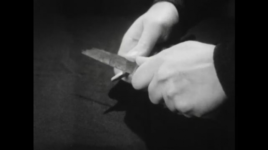 United States: 1940s: Hands sharpens pencil with knife. Lady removes robe in bathroom. Lady steps on bath mat in bath. Lady takes bath. Lady grabs soap