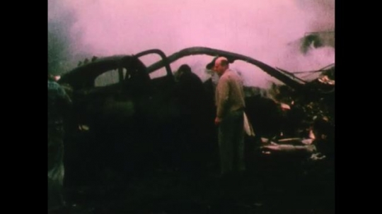 United States: 1950s: emergency services men at site of vehicle pile up. Men look for bodies at site of fire. Inside of car after fire. Man on stretcher after car crash.