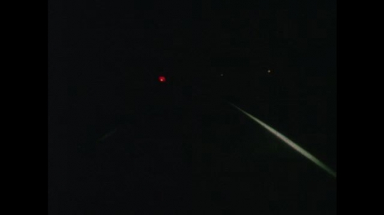 United States: 1950s: flashing red light on ambulance roof at night. Emergency response car at side of road at night.