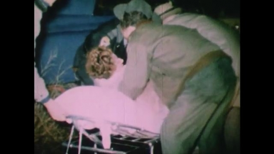 United States: 1950s: Men lay injured woman on stretcher by car crash. Men position inured lady on trolley. Injured man in seat of car after crash.