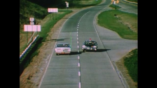 United States: 1950s: view of police car and vehicle driving along road.