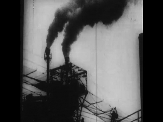 Russia: 1950s: smoke from factory chimneys. Industrial pipe. View over factory. Soldiers crouch and shoot guns. Women and children walk across field in snow. People flee.