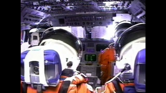 UNITED STATES: 2000s: Astronauts sit inside space shuttle cabin during flight. Monitors flicker. View over astronauts' shoulders.