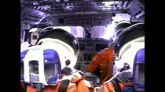 UNITED STATES: 2000s: Astronauts sit inside space shuttle cabin during flight. Monitors flicker. View over astronauts' shoulders. Astronauts close visors