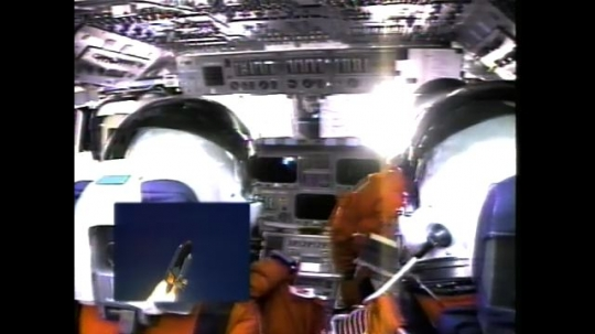 UNITED STATES: 2000s: astronauts shaken inside cabin during launch. View over shoulder of astronaut. Shuttle taking off.