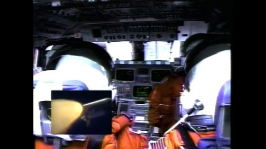 UNITED STATES: 2000s: astronauts shaken inside cabin during launch. View over shoulder of astronaut. Shuttle taking off. Shuttle splits into components.
