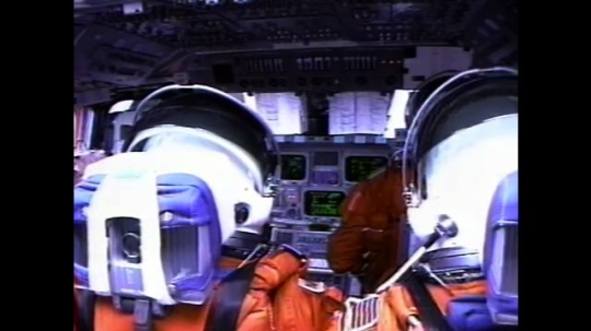 UNITED STATES: 2000s: astronaut opens visor during flight into space. View over astronaut's shoulders. Monitors inside shuttle cabin.
