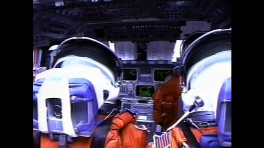 UNITED STATES: 2000s: Astronauts sit inside space shuttle cabin during flight. Monitors flicker. View over astronauts' shoulders. Astronaut presses buttons. Astronaut writes notes on pad.