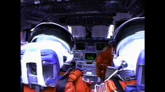 UNITED STATES: 2000s: Astronauts inside shuttle during flight. Monitors flicker. View over astronauts' shoulders. Light reflects on space suit. Astronaut presses buttons. Astronaut checks list.