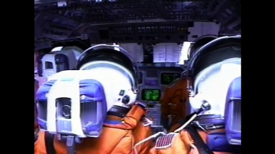 UNITED STATES: 2000s: Astronauts sit inside space shuttle cabin during flight. Monitors flicker. View over astronauts' shoulders. Astronauts unbuckle suits