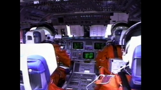 UNITED STATES: 2000s: Astronauts sit inside space shuttle cabin during flight. Monitors flicker. View over astronauts