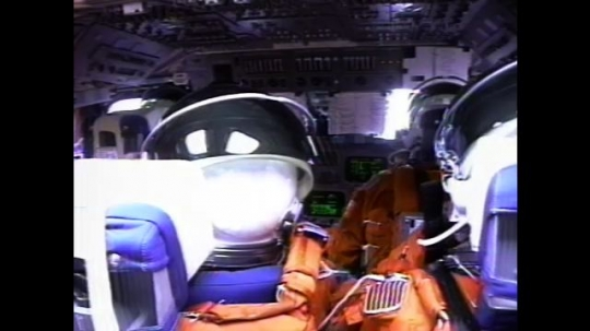 UNITED STATES: 2000s: Astronauts inside cabin during flight. Astronauts unbuckle suits. Particles in cabin. Astronaut changes gloves. Astronaut takes off helmet. Headphone floats in microgravity.