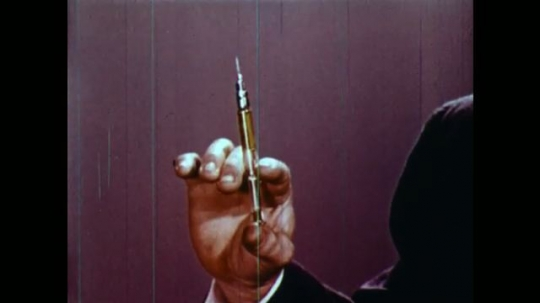 UNITED STATES 1950s: Hand pushes syringe / Man talks into camera, turns to chalkboard, chemical compound appears on board.