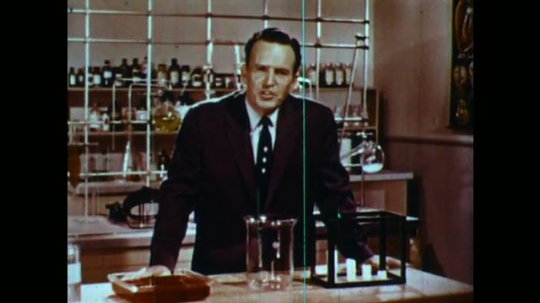 UNITED STATES 1950s: Man in lab talks into camera, picks up can.