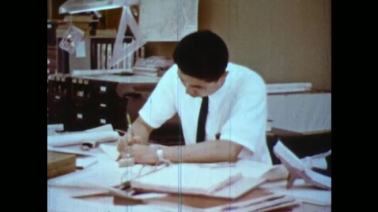 UNITED STATES 1950s: Man at desk / High angle view of desk / Man looks at ruler / Close up of ruler / Hands hold paper with equations / Pan across equations / Men at desk.