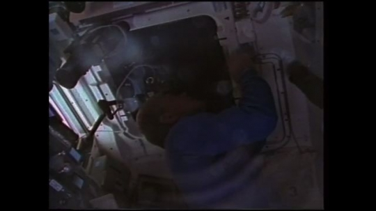 UNITED STATES: 1980s: astronaut undertakes engineering research in space. Astronaut films through window of space shuttle.