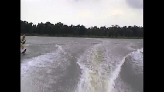 UNITED STATES: 1990s: water skiing on lake behind boat. Slow motion fall into water.