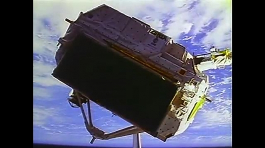 UNITED STATES: 1990s: satellite in space above Earth. Animation of satellite in space.