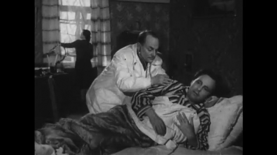 RUSSIA: 1950s: doctor listens to patient's chest with stethoscope. Man in bed at home.