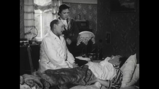 RUSSIA: 1950s: doctor and lady speak to patient. Man in bed at home. Doctor puts on glasses and writes notes.