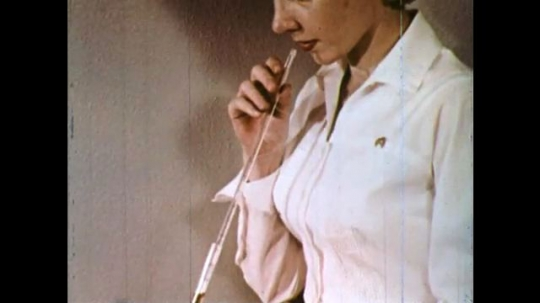 UNITED STATES 1960s: Woman puts long tube in mouth. Tubes labeled 1 and 2 stand next to label that says