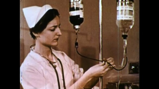 UNITED STATES 1960s: Nurse checks flow of tubes. Drip of blood. Hands use stick to take blood out of tube and swirl on glass slide. Hands put tube away and picks up glass slide.