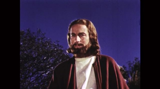 UNITED STATES: 1950s: Actor dressed as Jesus talks to disciples on mountain side.