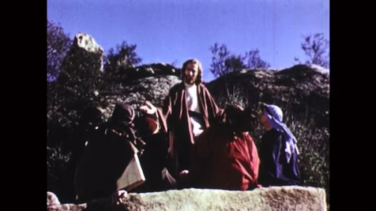 UNITED STATES: 1950s: men sit and talk on rock on mountain. Jesus talks to disciples.