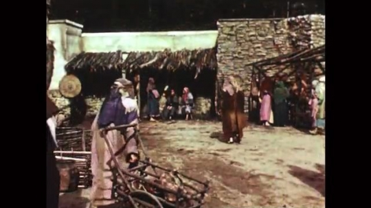 UNITED STATES: 1950s: people walk through ancient town. Temple rulers listen to Jesus speak.