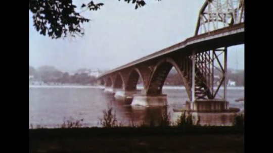 United States: 1960s: Steel bridge across wide river. Waterfalls on river. Panoramic view of Niagara Falls from top.