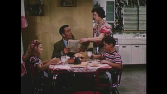 United States: 1950s: Lady takes newspaper from man at table. Lady serves dinner to man. Family at table. Lady works in garden. Lady plants roses. Close up of meat.
