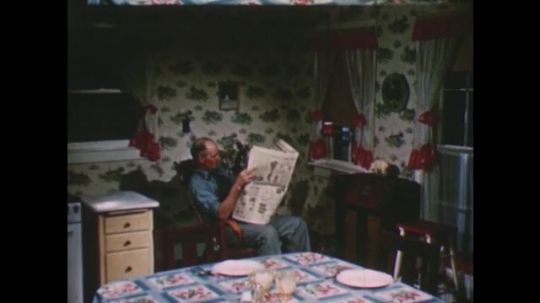 United States: 1950s: Man reads newspaper in kitchen. Man turns on radio. Close up of old radio. Man listens to old radio.