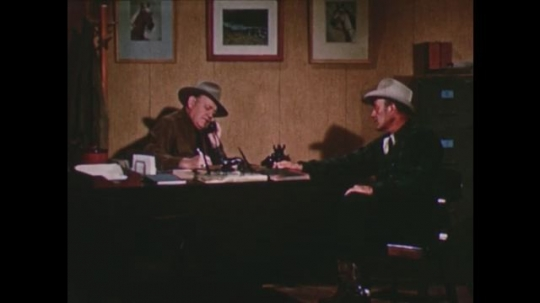 United States: 1950s: Two men in cowboy hats in office.