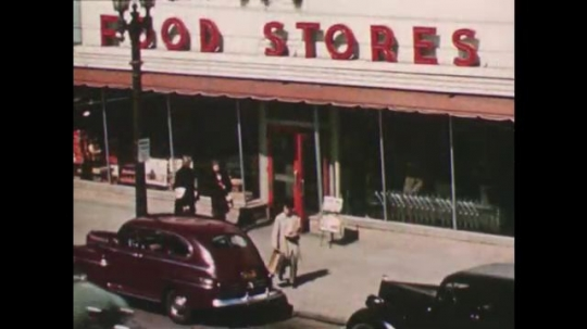 United States: 1950s: shoppers leave food store. Man clocks paper at cattle market.