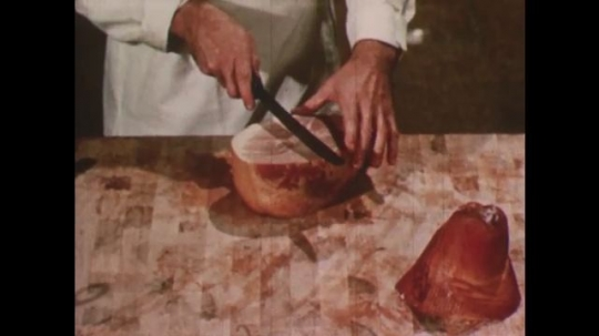 United States: 1950s: Butcher slices meat on block. Butcher talks to lady