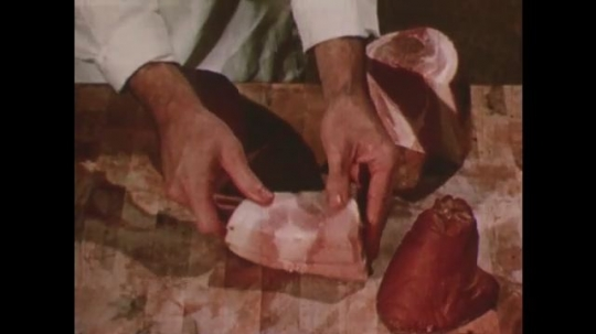 United States: 1950s: Hands place meat on block. Lady and man talk in butcher