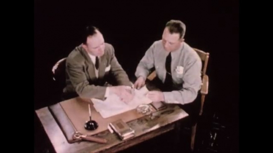 UNITED STATES 1950s: Man passes a paper to coworker . Man stands next to chalkboard with a drawing of a four intersection road. Man draws an