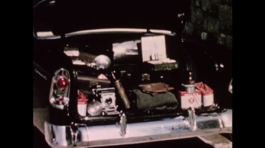 UNITED STATES 1950s: Open full trunk of car. Policeman with whistle in mouth waves cars on road. Room of policemen with two men in front of room. Two boards on the wall.