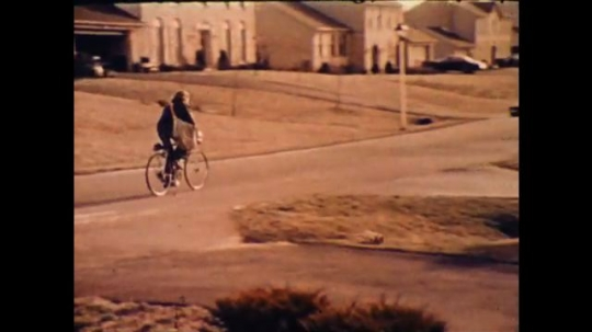 United States: 1970s: Girl on bicycle in street. Person runs along street. Man runs to door. Man knocks on house door.